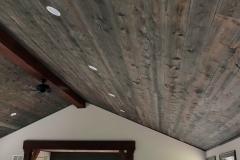A vaulted ceiling is adorned with distressed, grey stained lumber, recessed lighting, and a central, dark cherry stained beam.