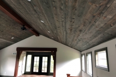 At the peak of a grey stained vaulted ceiling is a central, dark cherry stained beam.