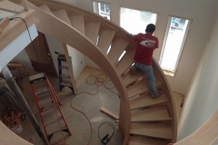 An incomplete, custom spiral staircase project with a worker halfway up the stairs