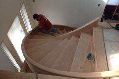 A second view of a worker partially up the stairs in an incomplete custom spiral staircase project