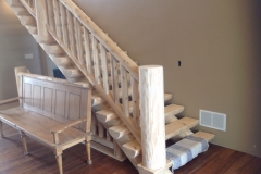 A view of a cabin-like staircase and wooden bench made from unfinished, unpainted lumber