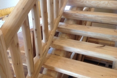 A closer view of the wooden staircase that reveals knots and millwork quirks that creates character in any lumber project