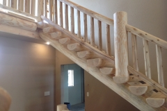 A view of the custom lumber staircase that shows where the stairs meet the second floor of a home