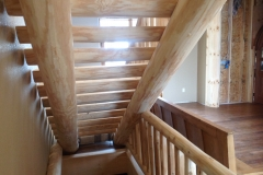 Beneath some custom stairs is basement or cellar access that's surrounded by matching wooden railing