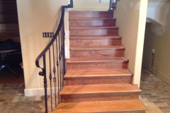 Wrought iron railing follows the length of a medium-stained, indoor wooden staircase