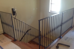 Wrought iron railing lines the second floor, indoor stair area of a two story house