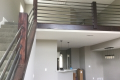 A lofted second floor is accessible from a modern staircase made from dark wooden posts and metal piping