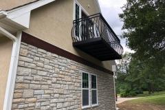 Ground level outdoor view of new, custom, dark metal balcony railing