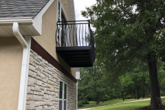 A second outdoor view from ground level revealing a dark metal balcony railing with convex rails