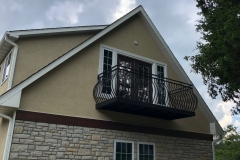 A custom project has rendered a dark metal balcony railing that has a convex curve to the bars.