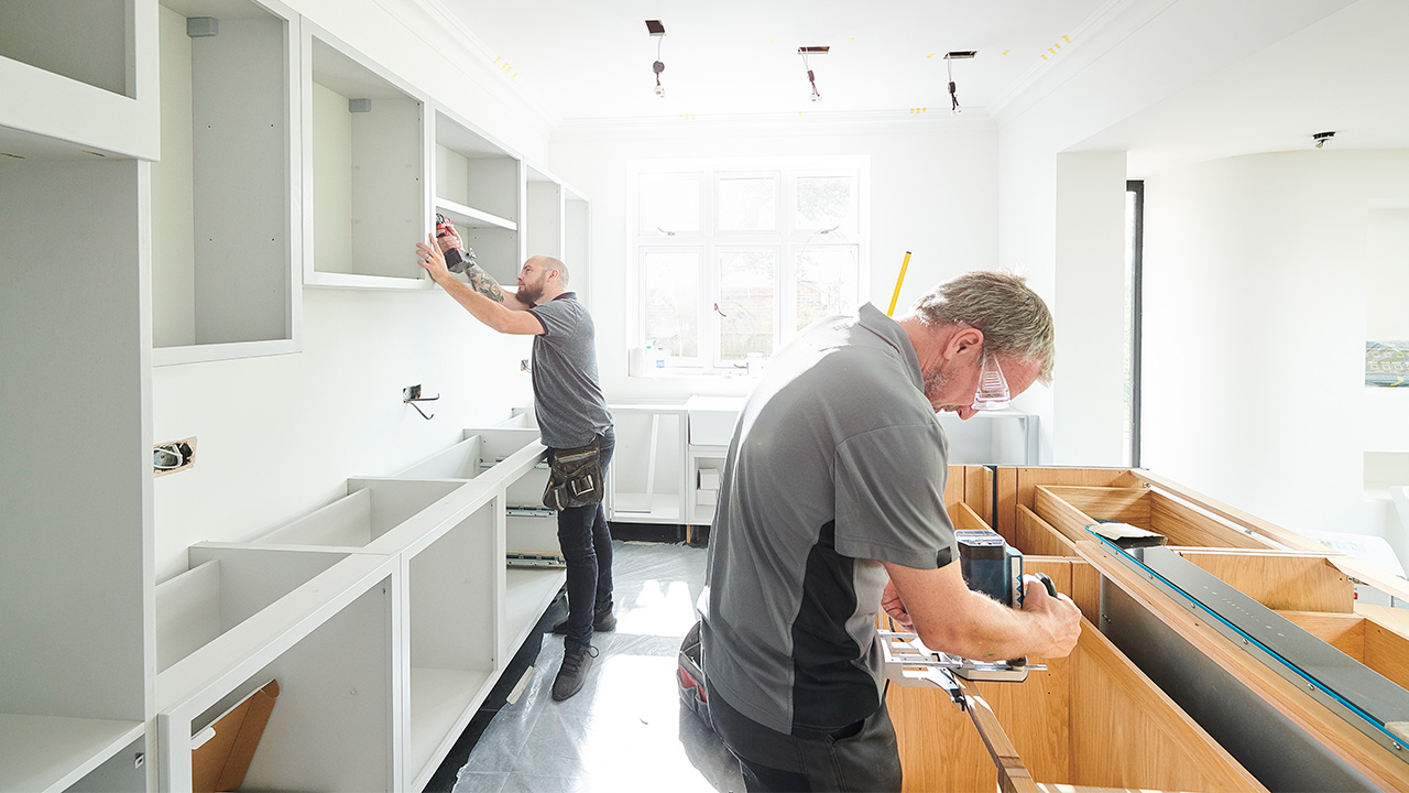 Two contractors working on white kitchen remodel.