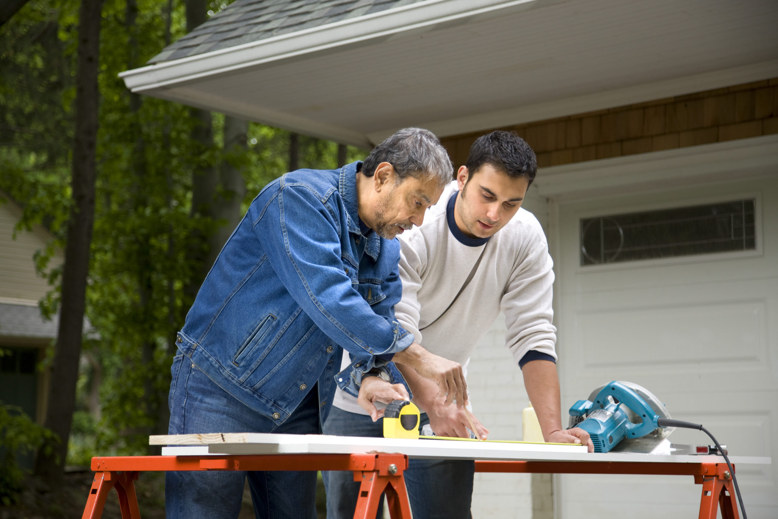 Father and adult son working on home project in driveway