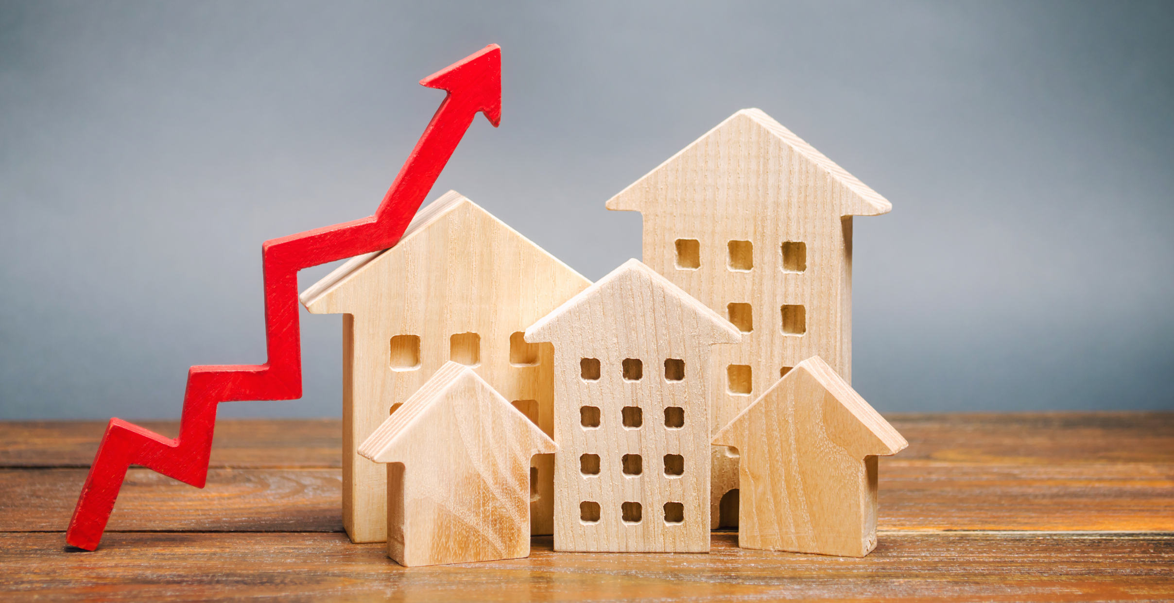 Miniature wooden houses with arrow sloping up to symbolize increasing home sales